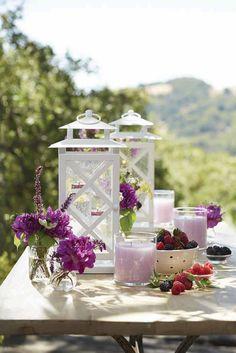 Kesäinen terassipöytä saa juhlavuutta, kun sen somistaa lyhdyillä ja hohtavilla GloLite-kynttilöillä.