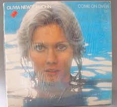 Olivia Newton John Come On Over 1976 Own an original vinyl!!  This record is in Near Mint (NM) Condition. Plays Beautifully! The cover still has the plastic cover. It is in near Near Mint (NM), only two minor dents at the corners where the album opens. Original dust cover is also in excellent condition.