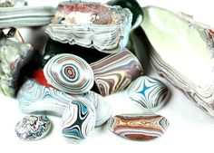 """Fordite jewelry pieces are each original works of art. """"Detroit Agates"""" are created by using the remnants of paint left behind on the pipes and pallets of spray booths in the old Ford plants. Each time a vehicle was painted in the spray booth a new layer of paint would dry, and then build up in the pipes and on the pallets."""