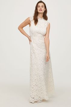 Cream. Long lace dress with a small, scalloped stand-up collar. Open section and concealed zip at back. Scalloped, butterfly sleeves, seam at waist, and gen