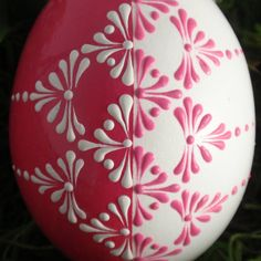 This is a chicken egg pysanka in white and pink, decorated with wax. To create this egg, I use the pinhead method also known as the drop-and-pull pinhead method. In this method, mostly used in Poland, the Czech Republic, Slovenia, and Lithuania, a pin stylus is used as a tool. The head of