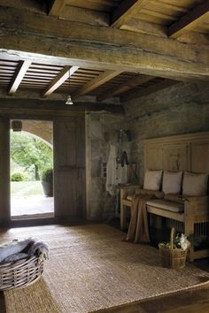 rustic entry of a home in cantabria with low exposed beam ceiling + high backed bench | interior design + decorating ideas