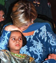 Princess Diana comforts 5-year-old Iqra Asif, sister of a cancer patient Khurram Zia, 14, during a function held at Imran Khan's Shaukat Khanum Trust Hospital in Lahore.