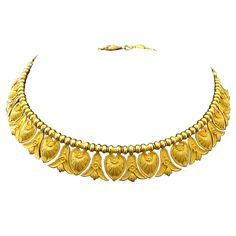 Antique Italian Gold Etruscan Style Necklace. An antique Italian 18 karat yellow gold Etruscan style necklace, Circa 1870s. The antique fitted box is signed Achille Squadrilli, Piazza Vittoria Napoli. The necklace is designed as alternating pendants of granulated bellflower and anthemion shield shaped sections, suspended from a gold braided chain with anthemion shield shaped hook and eye clasp. c 1870