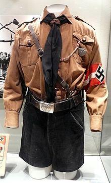 Uniforme a partir de los años 1930, diseñado por Hugo Boss: que consta de camiseta parda, pantaloncillos negros, cinturón de cuero con cierre, correa sujeta al hombro, pañoleta y cuchillo; Museo Estatal de Arte e Historia Cultural de Oldenburg.
