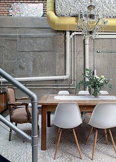Estilo industrial: Os tubos de PVC e os canos de metal se misturam aos dutos de ar-condicionado, pintados de amarelo, na sala de jantar