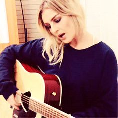 Perrie playing the guitar