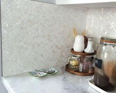 Perlmuttfliesen, die in einem Fischgrätmuster verkleidet sind, um eine neutrale Küche aufzutragen