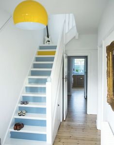 stairs painted in white and pastel blue, with a single step painted yellow, three pairs of shoes and a white electric guitar, large round yellow and white statement lamp, hallway decor, pale wooden floors, ornate golden frame