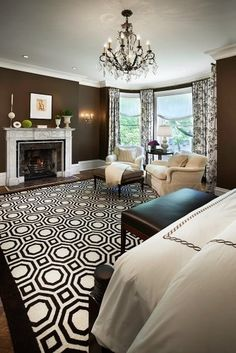 brown bedroom with crazy brown and white pattern rug. The rest of the room is a bit too traditional for my taste: chandelier, mantle decor, and curtains.