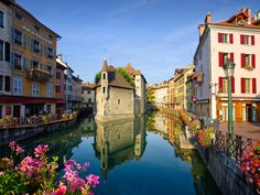 """Sometimes called """"the Venice of Savoie,"""" this lakeside Alpine town is treasured for its sloping hillsides and the small canals that wend their way through the streets. The small stone bridges over the canals make for perfect photo ops."""