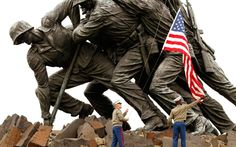 A US flag is lowered by Marine L Cpl Damien Brown and Cpl James White or a ceremony honouring members of the military at the Iwo Jima Memorial in Arlington, Virginia