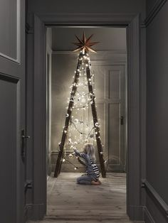ladder styled as christmas tree decor with string lights + ornaments [more colorful: https://pinterest.com/pin/282178732872080087/ ]