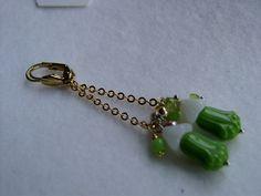 Der Traum der Blumenelfe, dieser Ohrring in grün.  Der Ohrring schwebt an einem Kettchen am Ohr, die wundervolle Jugendstilblüte schwingt im Sonnenlic