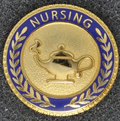 a Nursing pin with wreaths and Nursing Lamp Medpins.com also sells the nursing lamps and Nursing Caps so the graduation pictures look great!