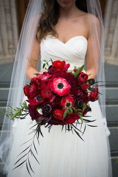"""Katie carried a textural red bouquet of anemones, ranunculus, poppies, peonies and fiddlehead fern, """"I cried when I saw my bouquet, it was so beautiful!"""" she says."""