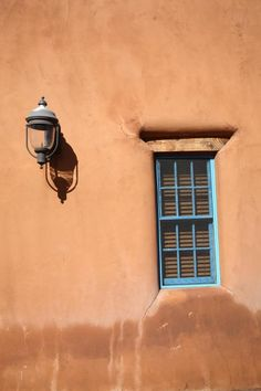 Santa Fe - Adobe Window and Light. New Mexico house features cracked adobe wall, small window, and old fashioned light fixture. It all shines on a Southwestern sunny day.