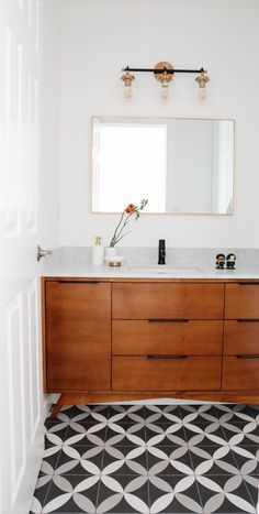 This mid-century bathroom is so beautiful and modern! We added a fun black and white tile design for the shower and flooring, rectangular mirrors, and rich brown cabinets. See more of this mid-century bathroom renovation in this Sunnyvale, CA home! Mid Century Modern Bathroom, Modern Bathroom Tile, Bathroom Tile Designs, Bathroom Interior Design, Mid Century Bathroom Vanity, Bathroom Ideas, Dining Table In Kitchen, Mid Century House, Beautiful Bathrooms