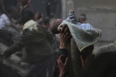 Men hold up a baby who survived what activists say was an airstrike by forces loyal to Syrian President Bashar al-Assad in the Duma neighbourhood of Damascus | Credit: Bassam Khabieh