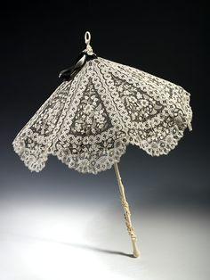 A parasol from the 1870s made of white lace over black silk with a carved elephant tusk ivory handle. The parasol was a popular accessory throughout the 19th century and was used to protect ladies from the effects of the sun at a period when pale skin was the height of fashion.
