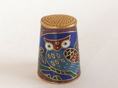 Vintage cloisonne owl thimble is in dark blues, red, green and black. It has white eyes that really stand out. Dimpled brass top. Here is how to