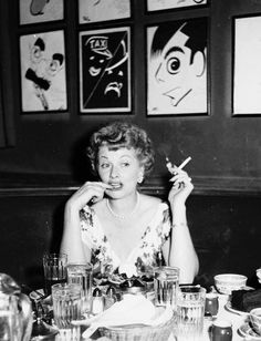 """Lucille Ball seated under the """"Amos 'n Andy"""" caricature at the Brown Derby."""
