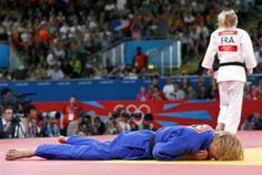 Austria's Sabrina Filzmoser lies on the mat after losing to France's Automne Pavia in the women's -57kg quarter-final judo.
