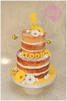 2 tier first birthday naked cake in yellow and white with a bubble bee theme and edible gerbera daisies. x