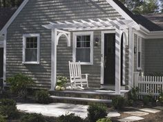 A traditional entry pergola frames this front door and small porch.