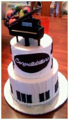 Two tier cake with piano theme on bottom tier and music notes floating arounding top tier with a baby grand topper.
