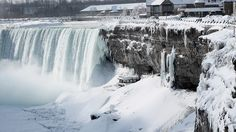 An unprecedented cold front has frozen parts of Niagara Falls, drawing tourists to document the rare event.