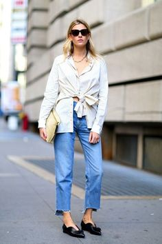 Camille Charrière steps out in a modern take on the classic button-down and jeans look. She refreshes the usual mix with a simple chain necklace, a striped tie-front shirt, slouchy raw-hem jeans and unique knotted pointed toe flats.