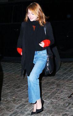 Emma Stone wears a red sweater, blazer, black scarf, raw-hem jeans, pumps, and a saddle bag