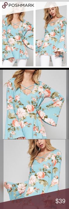 stunning blue floral bell sleeve top In a jersey knit fabric with a stunning bouquet against a soft blue with criss cross front and bell sleeves Tops