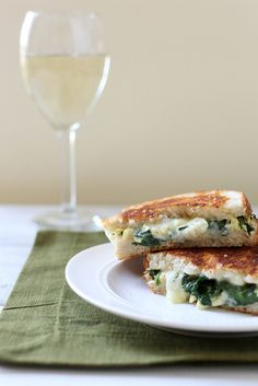 Spinach Artichoke Grilled Cheese  Yield: 2 servings  Ingredients    1 tbsp. olive oil  2 cloves garlic, minced  About 3 cups chopped spinach leaves, stemmed, washed and dried  Salt and pepper, to taste  1/3 cup artichoke hearts, chopped  2 tbsp. sour cream or Greek yogurt  1 cup freshly shredded cheese*  4 slices artisan bread, such as sourdough  Butter, for cooking