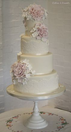 wedding cake, have the bottom ribbon part be pearls, and have the lace be champagne colored.