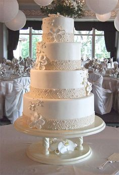 White Linen❤ How beautiful, white linen decor with a touch of summer fancy. Fondant bands accented in royal icing and edible pearls trimmed the base of each tier of this four tier beauty.  Stylized gumpaste flowers appear lighter-than-air as they drift up the sides of the tiers.