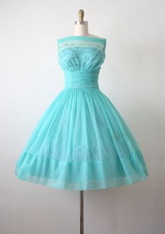 Vintage 1950s chiffon party dress in a rich teal blue. Classic cinched cummerbund waist and a full skirt with a built in crinoline. Sheer neckline
