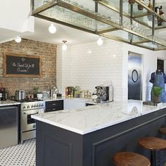 Love this kitchen. Brick wall, tile floor, open rack above for glasses.