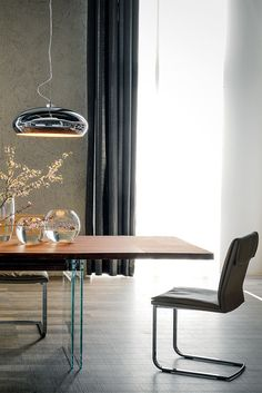 Ikon Drive, designed by Philip Jackson, is a gorgeous extendible table with 15mm extra clear tempered glass base and graphite beam. Top and extensions in Canaletto walnut, burned oak or natural oak with irregular solid wood edges.