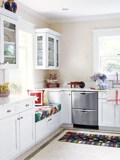 Kitchen With a View A well-placed window seat looks out to a gorgeous yard. The handmade quilts, rugs, and pillows add bursts of color to the all-white room. Read more: Country Kitchen - Kitchen Designs - Country Living --- eeek! i'm a fan of well placed windows. moooore natural light inside the house! weee! <3<3<3