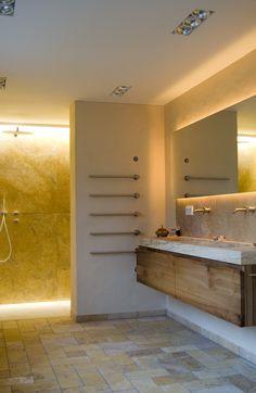 Bad in Travertin, Boden mit bodengleicher Dusche hinter der Trennwand, Wände und massiver Waschtisch - abgestimmt mit Holzmöbeln und Beleuchtung - perfekt oder?