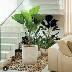 Jardim debaixo de uma escada branca com guarda corpo em vidro. Vasos cerâmicos sobre pedras.