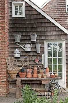 This circa-1900 oak woodworker's table was drafted into service as a potting station, then hung vintage pails and watering cans on this cottage's exterior wall.