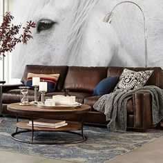 We aren't sure which we love more -- the amazing artwork or the perfectly worn in looking leather sofa. #gobigorgohome #sofaenvy #mypotterybarn #shoplinkinbio