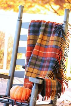 Plaid blanket thrown over a rocker with a basket of pumpkins and gourds.