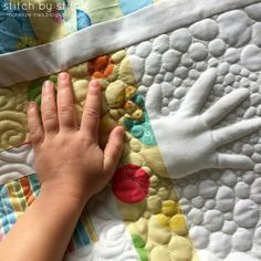 Quilt in a child's hand print - How cool for a family or grandparent quilt, or a baby quilt! I wouldn't stuff it, the one shown is too puffy for my taste. Just the contrast with closely-spaced background would make it clear enough for me.