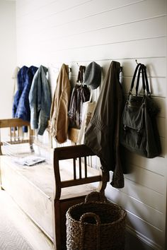This simplified mudroom provides a convenient spot to drop your coat and bags after a busy day. A vintage wooden bench is an ideal find and opens up for additional odds and ends to be stored.