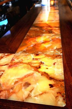 Amber onyx backlit bartop, rounded corners, wood bordering- visit globalgranite.com to see our onyx slabs.