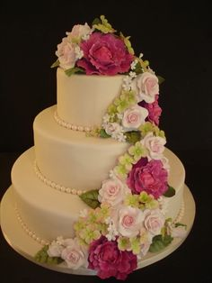 wedding cake with raspberry pink, pale pink, and green flowers
